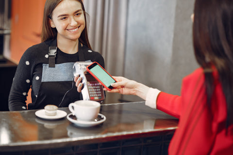 Barista and Customer, Why Your Coffee Shop Needs Social Media (and How to Do it)