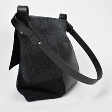 Knit-felted, ultra-fine merino wool handbag in Black Ombre. Vegetable tanned English bridle leather straps and trim with large flap and magnetic top closure. Handstitched, leather, patch pocket on the back. Made in Colorado.