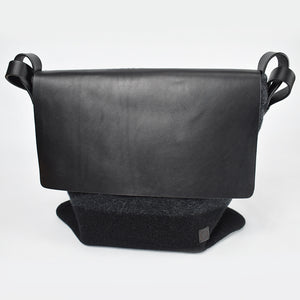 Knit-felted, ultra-fine merino wool handbag in Black Ombre. Vegetable tanned English bridle leather straps. One-inch wide with lacquer finished, brushed nickel hardware. Large leather flap with magnetic top closure. Made in Colorado.