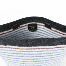 Unlined view of knitted, boiled, soft wool handbag in denim blue stripes on cream ground. Organic, renewable and toxin free.