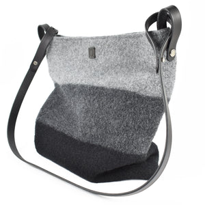 Knit-felted, ultra-fine merino wool handbag in Licorice, Onyx and Thunder. Vegetable tanned English bridle leather strap and trim with lacquer-finished, brushed nickel hardware.