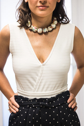 Woman with a white top and a statement necklace