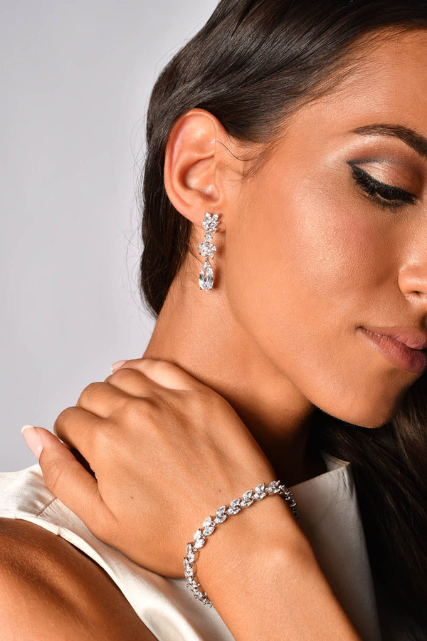 Woman wearing a crystal bracelet and crystal drop earrings