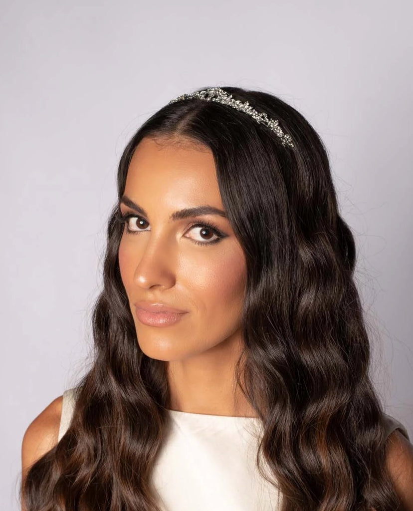 Bride wearing a silver tiara with peaks of sparkling gemstones in a flowing floral pattern