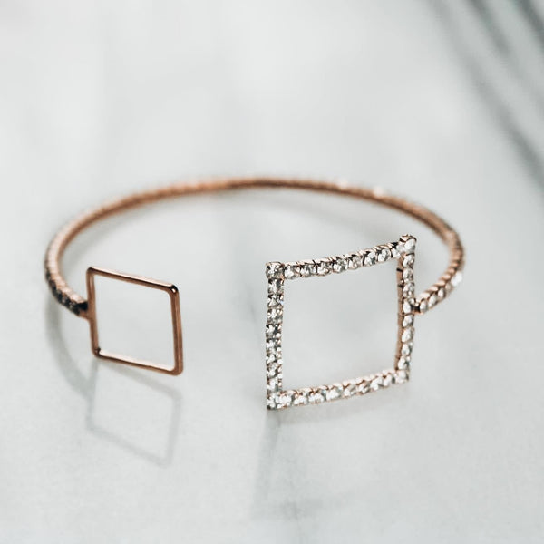 Gold bracelet with two squares encrusted with cubic zirconia on white background