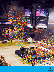 Primary latex balloons dropping inside a coliseum