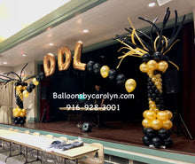 Black and Gold Balloon pillars on each side of the stage with a connecting balloon arch and long skinny balloons shooting out the top of the pillars