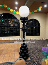 Balloon Pillar on the corner of a dance floor.  The pillar looks like a Mardi Gras Street Sign