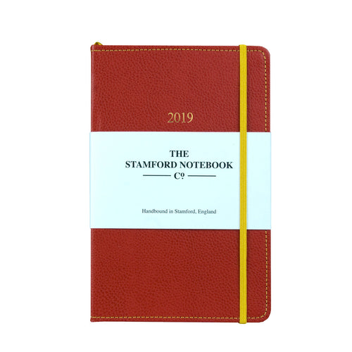 red leather diary with yellow stitching