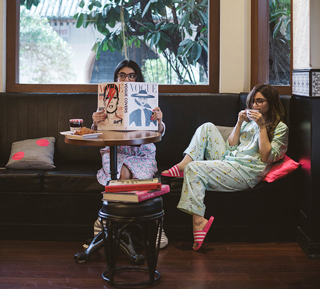 Two women lounging inside with books and magazines wearing Dandelion Dreams Pajamas