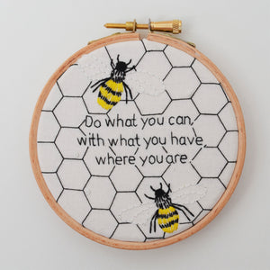 "Hand embroidery hoop of 2 bees on a monochrome honeycomb background quote reads ""Do what you can, with what you have, where you are"""