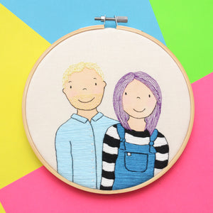 A hand embroidery and watercolour portrait of a couple. The man on the left has blonde hair and a pale blue shirt. The woman on the right has purple hair, a black and white stripey top and teal dungarees.