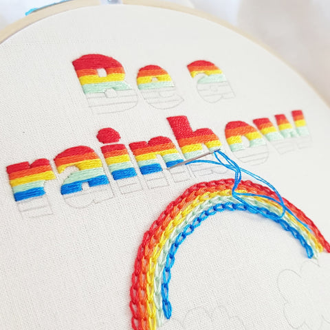 hand embroidering a rainbow and colourful text