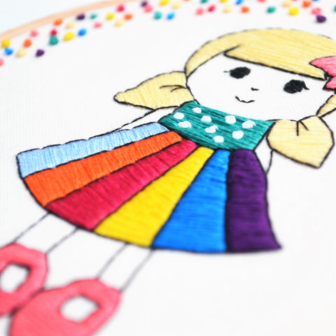 hand embroidery hoop art of a doll in a rainbow skirt