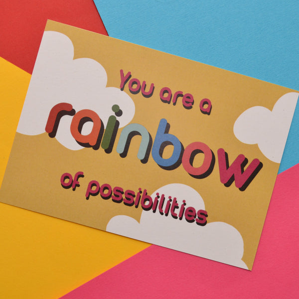 You are a rainbow of possibilities postcard in red and rainbow colours on a yellow and white cloud background