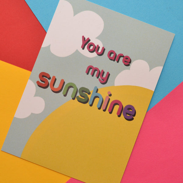 You are my sunshine postcard in red and rainbow colours. The background is a bright yellow sun, blue background and white clouds.