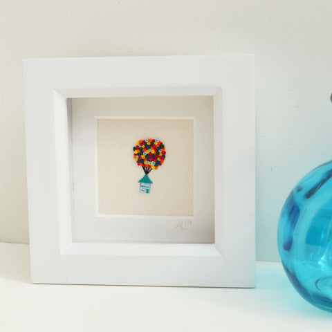 A hand embroidery of a little house lifted up by many tiny rainbow balloons framed in a small white box frame