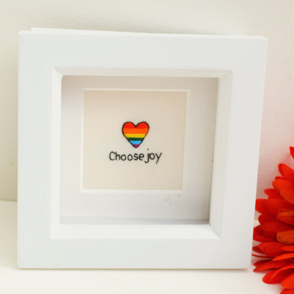 A miniature hand embroidered rainbow striped heart above the text choose joy in a small white box frame