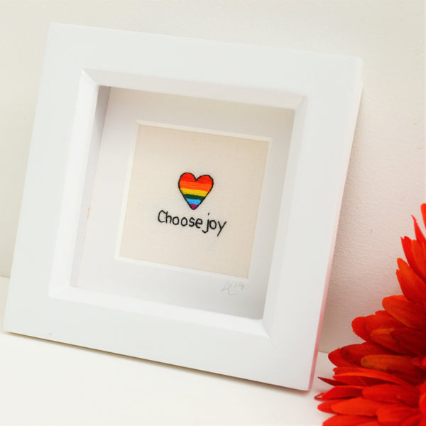 A rainbow striped heart hand embroidered above the tiny stitched text choose joy in a white box frame