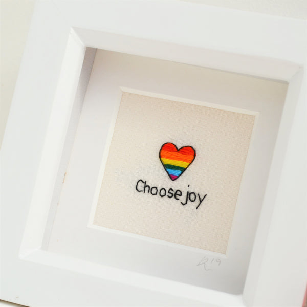 A close up view of the rainbow heart embroidery with the stitched text choose joy beneath it