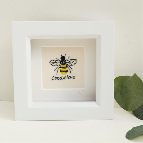 A miniature hand embroidered bee above the text choose love. Framed in a white box frame