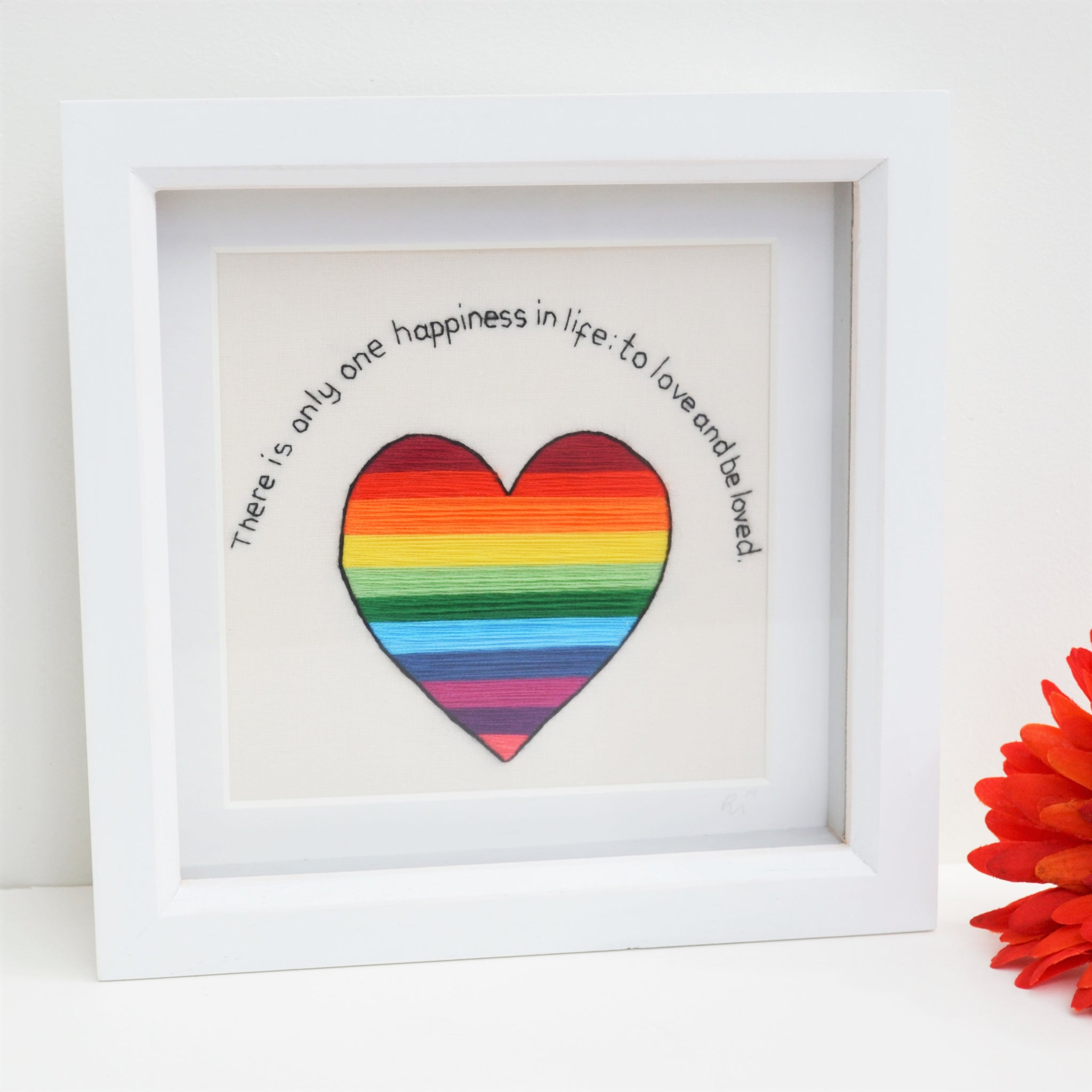 A hand embroidered rainbow striped heart and the text reads There is only one happiness in life: to love and be loved