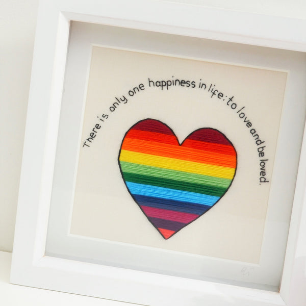 A close up view of a rainbow striped heart underneath the text There is only one happiness in life: to love and be loved