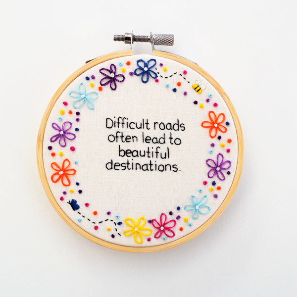 A hand embroidery hoop with the quote difficult roads often lead to beautiful destinations surrounded by colourful flowers