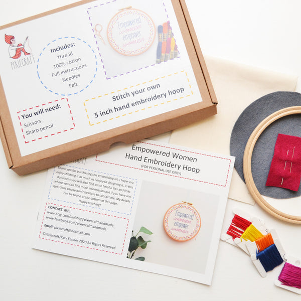 An aerial shot of the hand embroidery kit. There is a brown kraft box with a Pixiecraft label on, an instruction booklets and some kit materials laid out flat