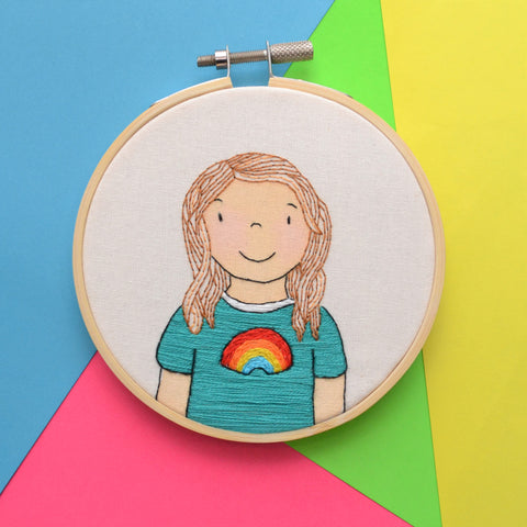 A mixed media hand embroidery hoop illustration of a small girl. She has pale skin, rosy cheeks and wavy brown hair. She has green tshirt with a rainbow it. The hoop is sat on a multicoloured background