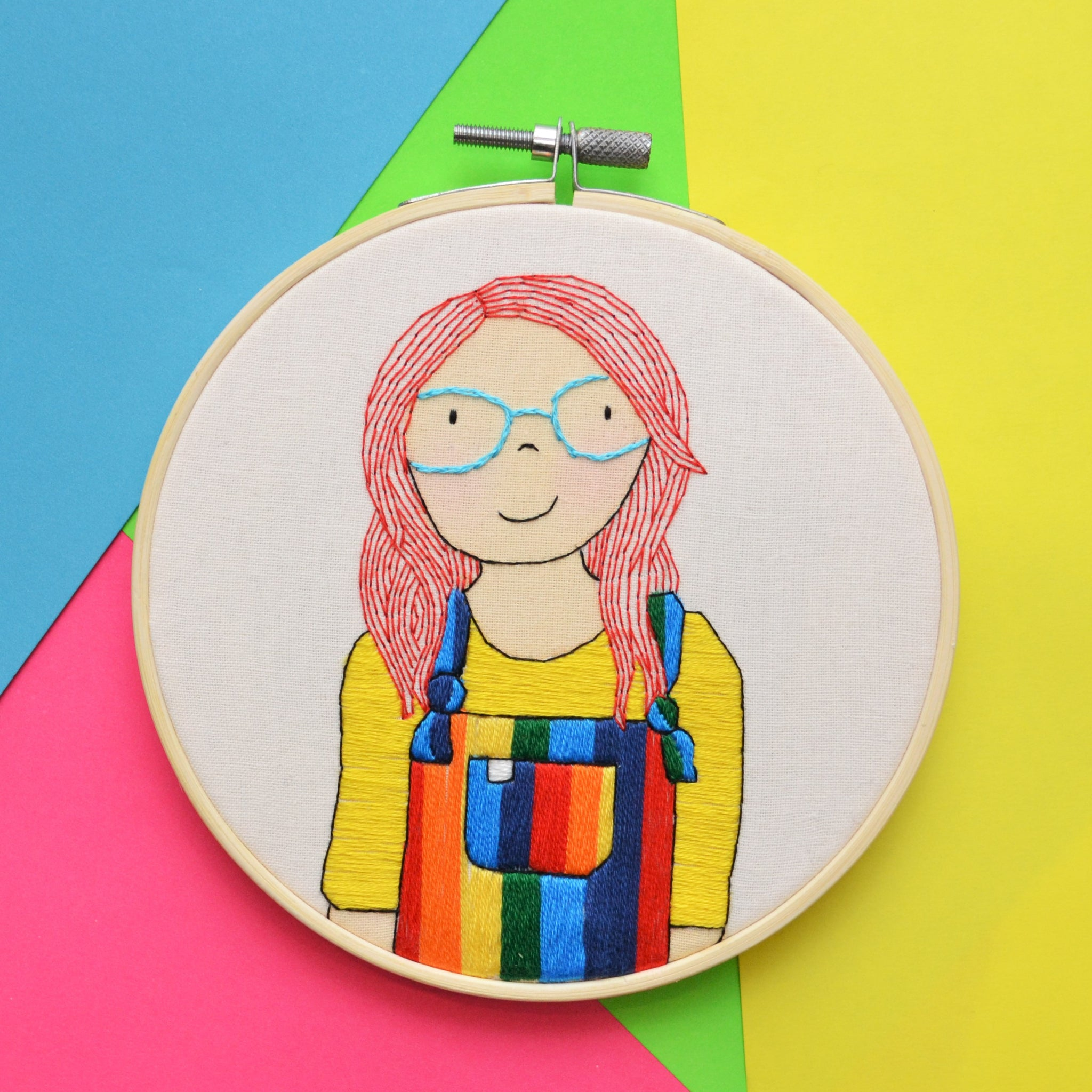 A mixed media hand embroidery illustration of a female with bright red hair and blue glasses. She is wearing rainbow dungarees and a bright yellow top. The hoop is sitting on a multicoloured background.