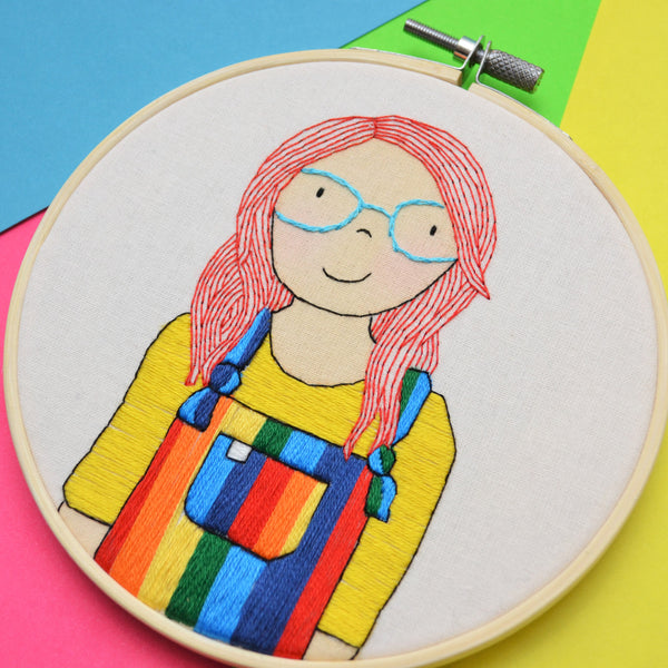 A side on view of a portrait hoop of a light skinned female with bright red hair and blue glasses. She is wearing rainbow dungarees and a bright yellow top.