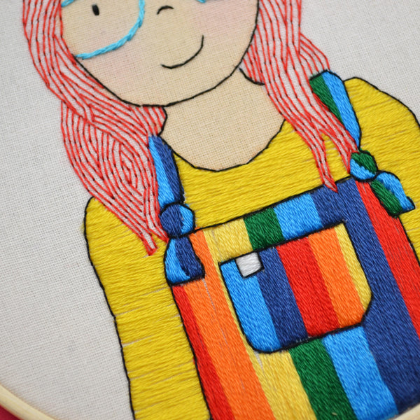 A close up view of a hand embroidered portrait. It shows the detail of the rainbow dungarees and hand stitched bright red hair.