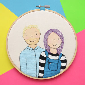 A hand embroidered mixed media portrait of a while couple. The man on the left has light blonde hair and stubble and is wearing a pale blue shirt. The woman on the right has bright purple hair, teal dungarees and a black and white striped top. The hoop is sat on a multicoloured background