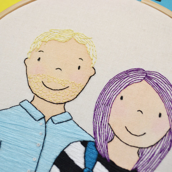 A close up view of the faces of the couple on a mixed media hand embroidered portrait hoop