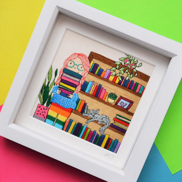 An original piece of mixed media hand embroidery. This pieces shows a fair skinned girl with long bright red hair and blue glasses holding a pile of colourful books. She is wearing a cosy textured jumper and rainbow leggings. Behind her is a tall bookcase full of colourful books. On the bookcase is a trailing green plant in a pink pot. Asleep on the bookcase shelf is a grey cat. On the other side of the girl is a tall plant in a pink and grey plant pot.