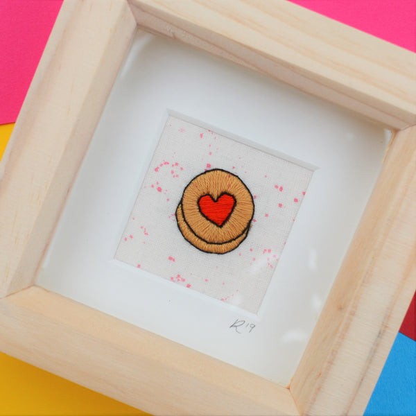 A hand embroidered jammy dodger biscuit framed in a deep set box frame on a multicoloured background