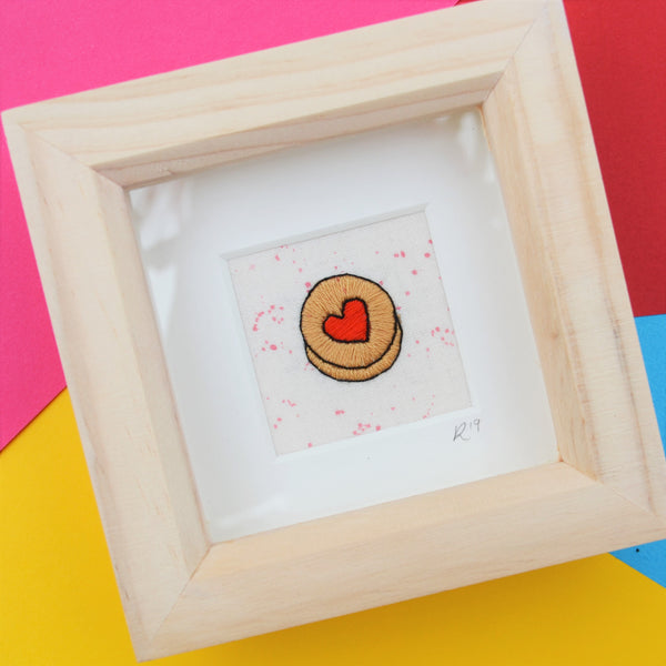 A box frame sits on a colourful background inside is a tiny hand embroidered jammy dodger biscuit