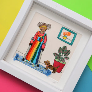 This pieces shoes a black girl wearing bright rainbow dungarees. She has brown curly hair, bright yellow glasses and odd socks. She is leaning on a pair of crutches and is stood alongside a large calathea plant and brown speckled sausage dog. On the wall is a green frame with a picture of a yellow pot with orange flowers in and on the floor is a textured weaved blue rug with tiny tassels.