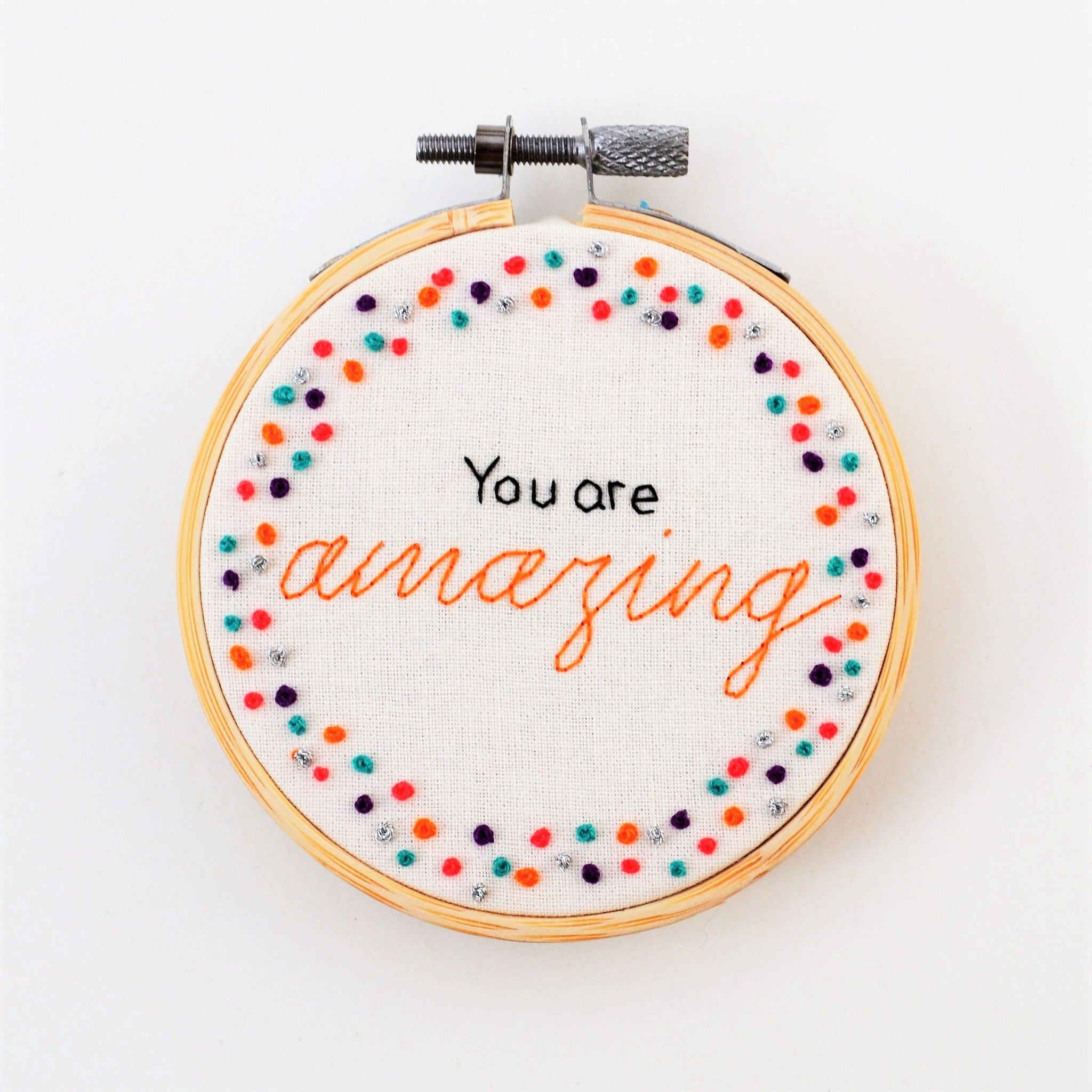 A small miniature hand embroidery hoop reading You are amazing surrounded by colourful and shiny silver french knots on a while background