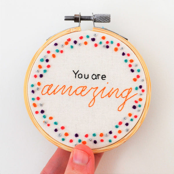 A hand holding up a miniature embroidery hoop which reads you are amazing surrounded by colourful french knots on a white background
