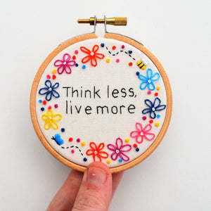 a mini embroidery hoop with the quote think less live more surrounded by colourful flowers