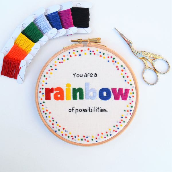 A hand embroidery hoop reading You are a rainbow of possibilities surrounded by rainbow french knots