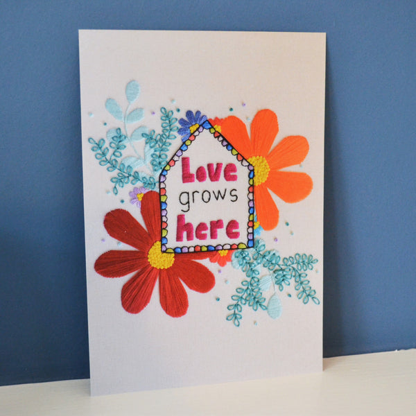 A photographic print of a piece of hand embroidery showing the love grows here design.
