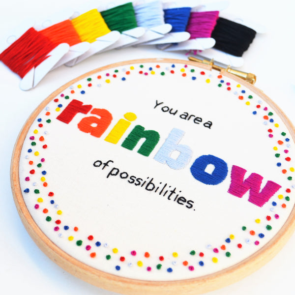 A hand embroidery hoop art reading You are a rainbow of possibilities in rainbow colours alongside rainbow coloured bobbins of thread.