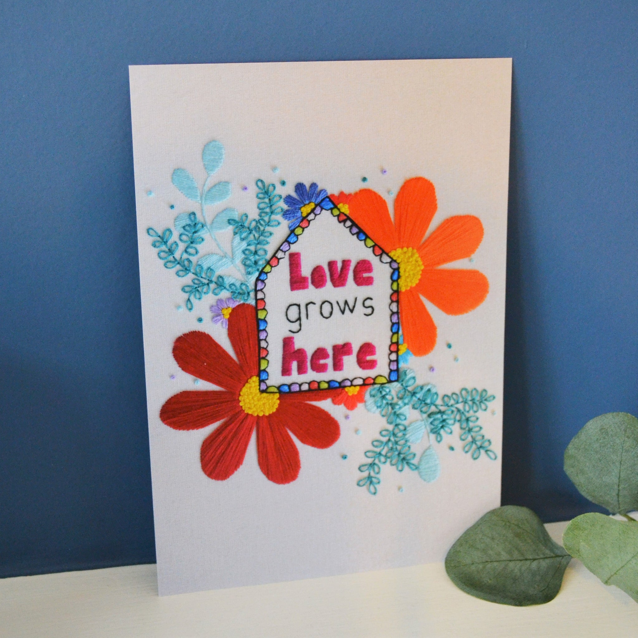 An a5 print of a hand embroidery with the quote love grows here at the centre of a basic house shape. Surrounding the house shape is a range of bright coloured flowers and leaf patterns. The print is propped up against a blue wall next to a small houseplant