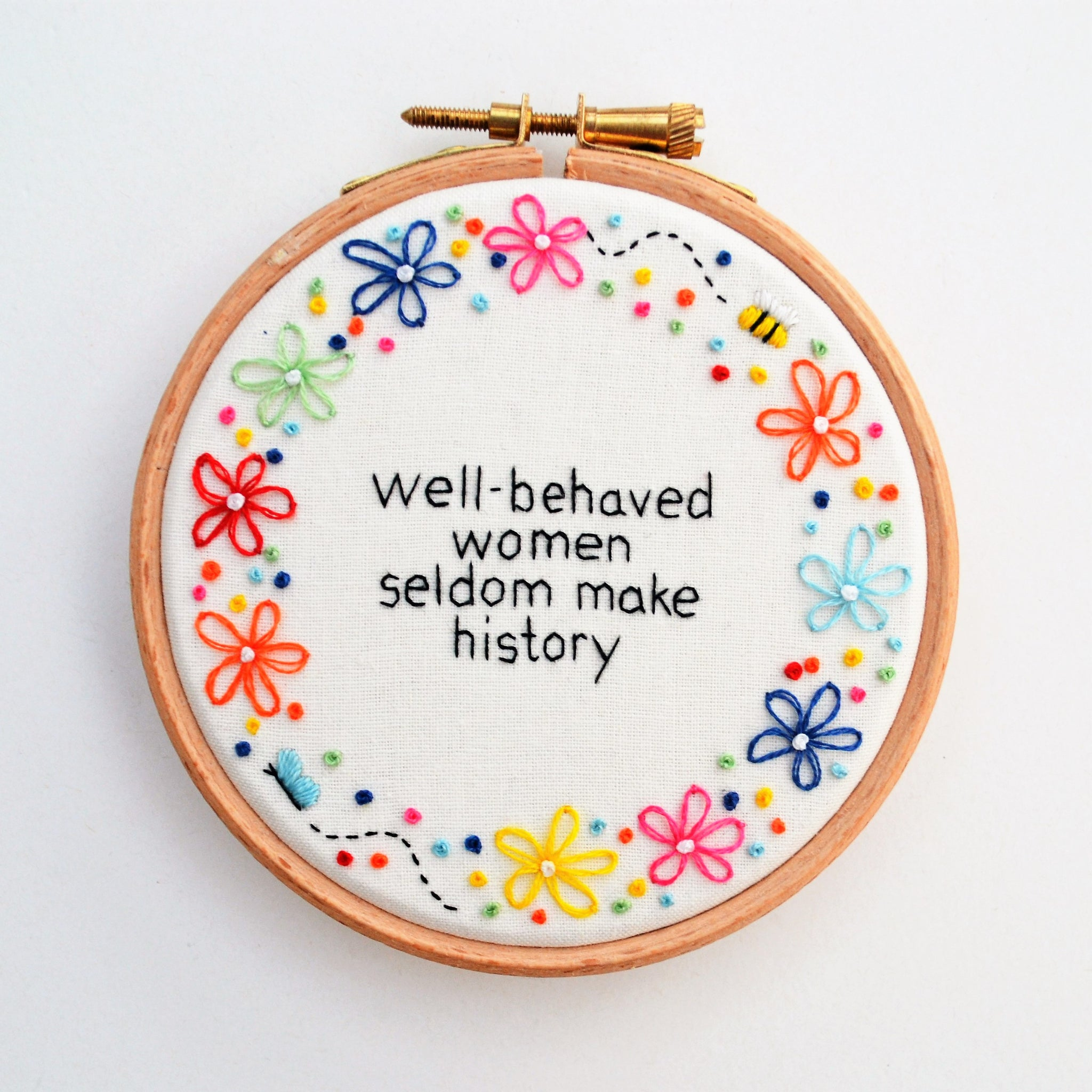 Hand embroidery hoop of the quote well-behaved women seldom make history surrounded by colourful flowers on a white background