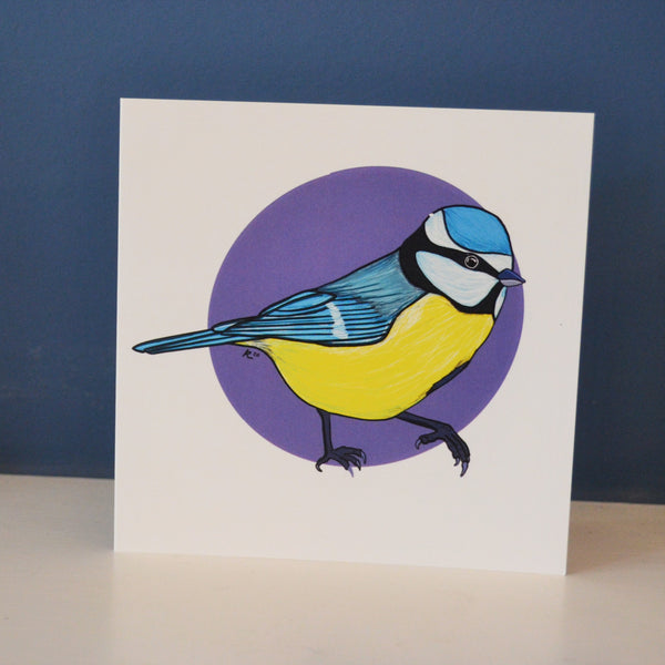 A digitally illustrated blue tit card on a purple spot background surrounded by white