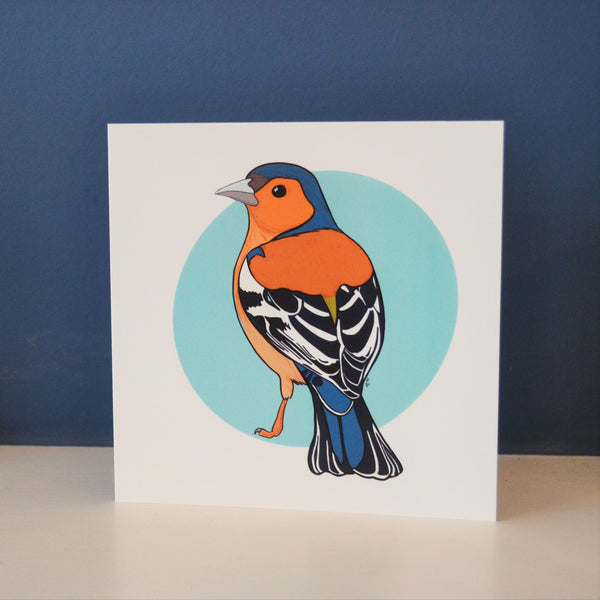 A digitally illustrated chaffinch on a pale blue spot background surrounded by white