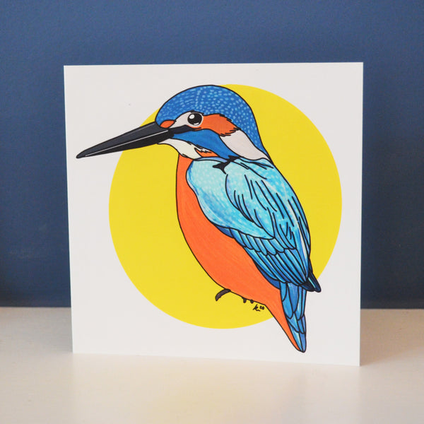 A digitally illustrated kingfisher on a bright yellow spot background surrounded by white